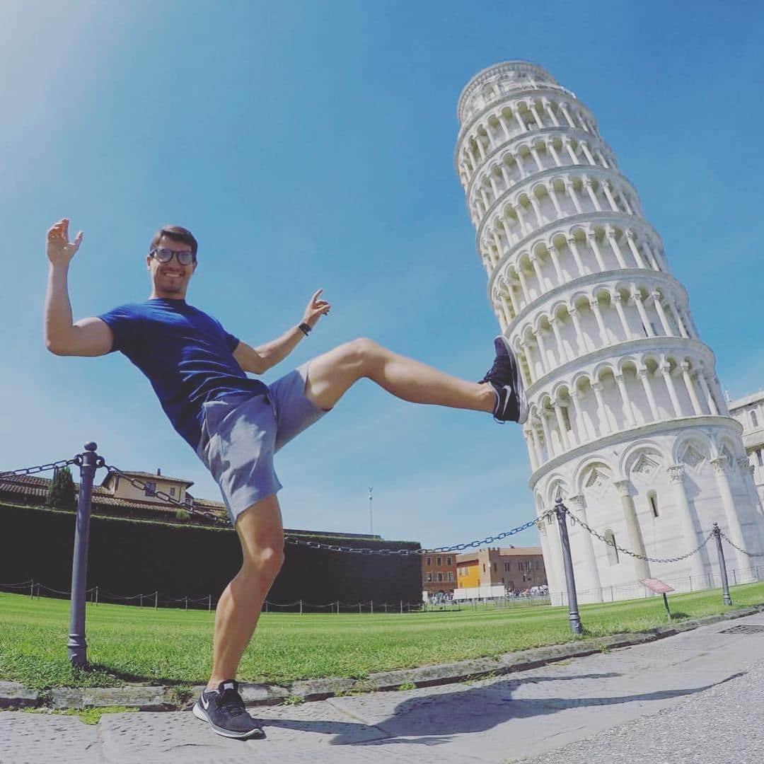 парень толкает ногой пизанскую башню