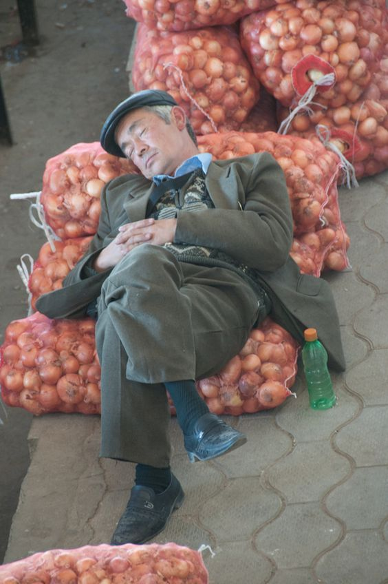 мужчина спит на мешке с луком