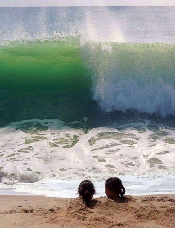 волна накатывает на девочек, закопанных в песок