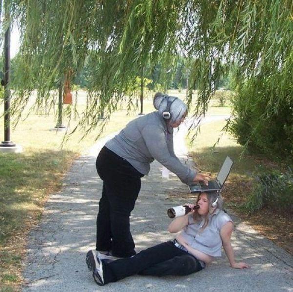 девушка пьет из бутылки с ноутбуком на голове
