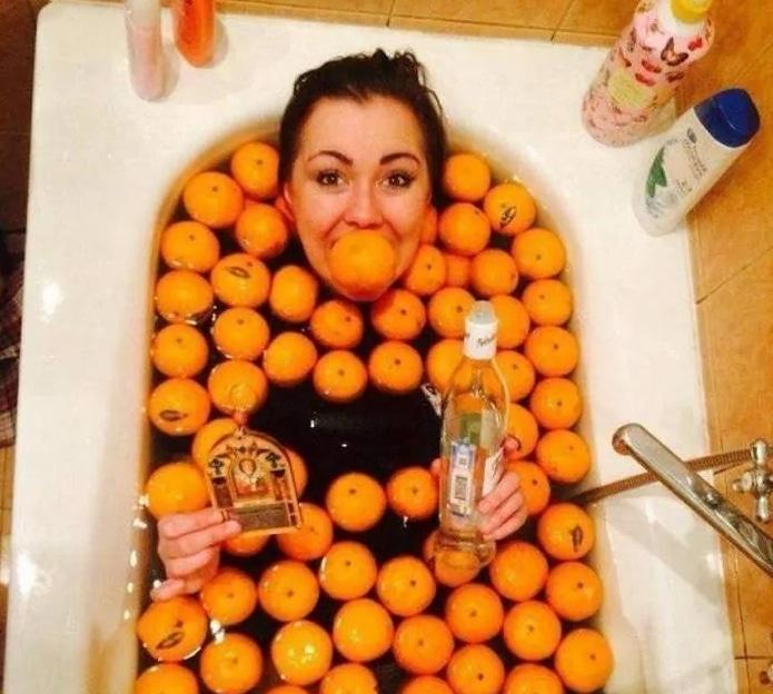 девушка лежит в ванне с апельсинами
