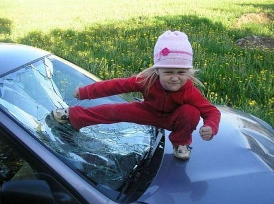 Девочка бьет ногой в разбитое стекло машины