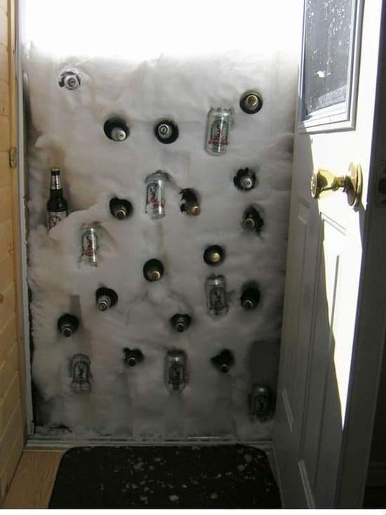 Бутылки в сугробе снега, засыпавшем дверь