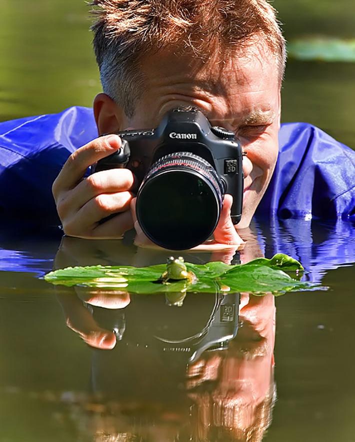 Фотограф в воде снимает лягушку