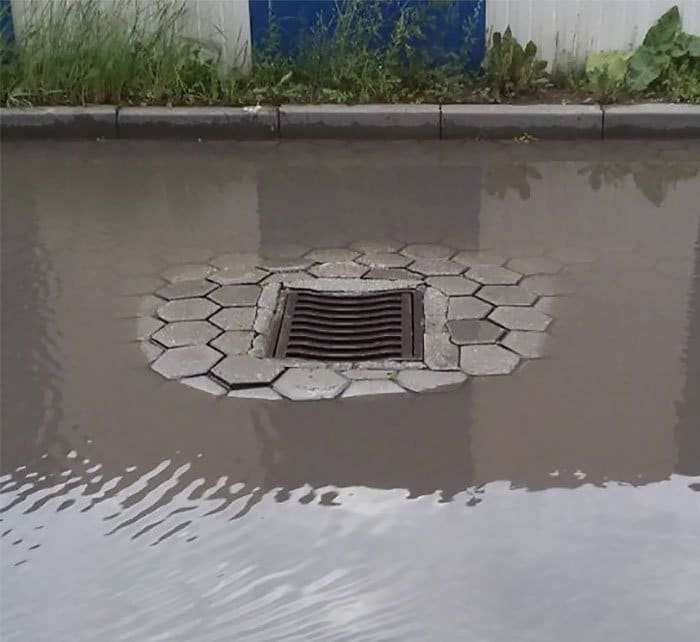 Канализационный люк на возвышенности, окруженный водой