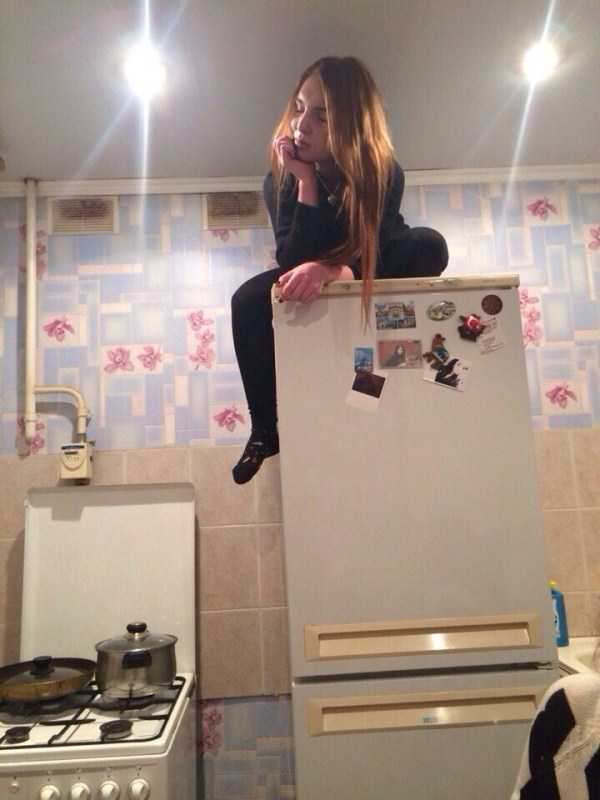 девушка сидит на холодильнике