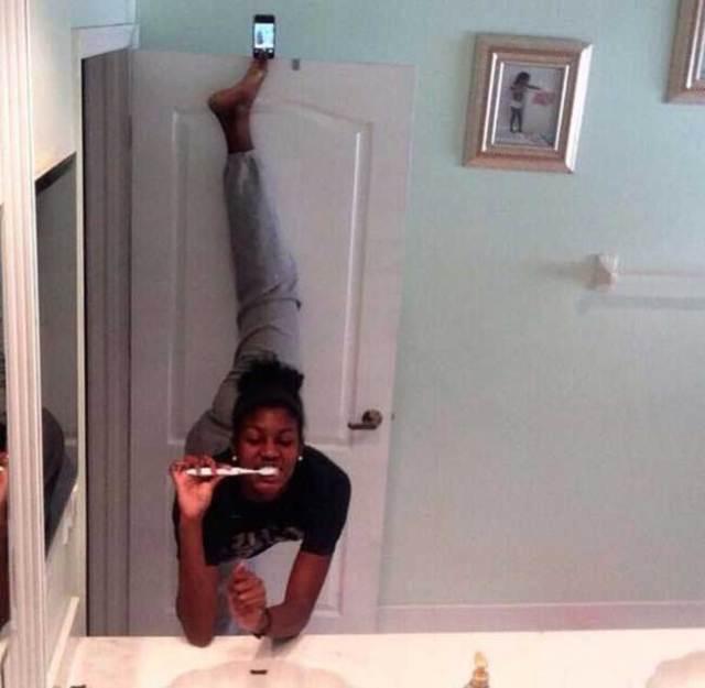 чернокожая девушка чистит зубы на шпагате