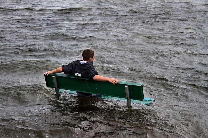 парень сидит на лавке в воде