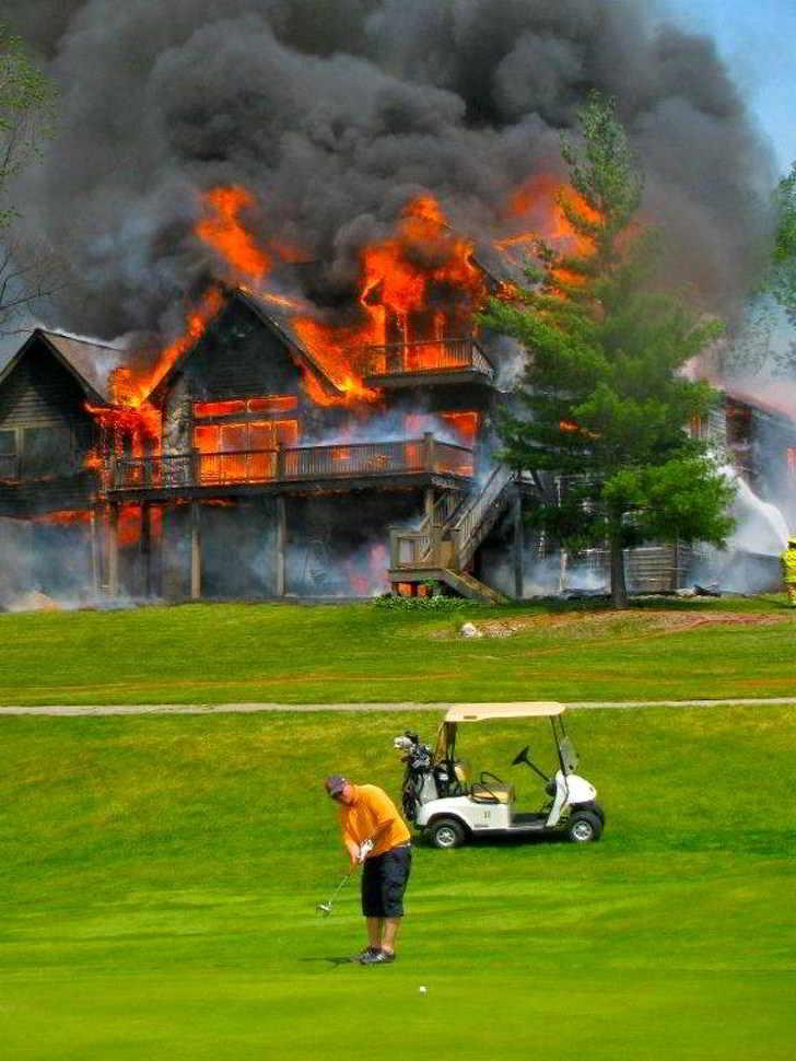 мужчина играет в гольф на фоне горящего дома