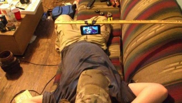 парень смотрит видео на телефоне, лежа на диване