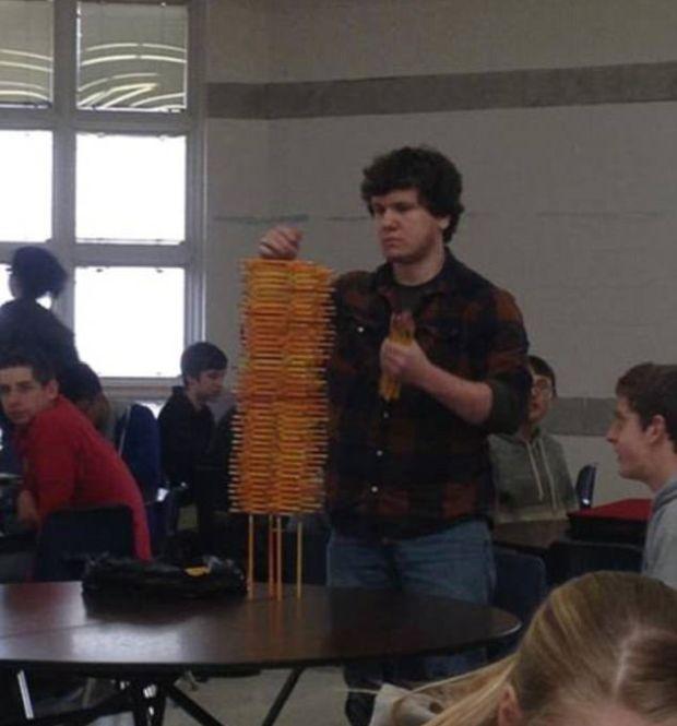 парень складывает башню из карандашей