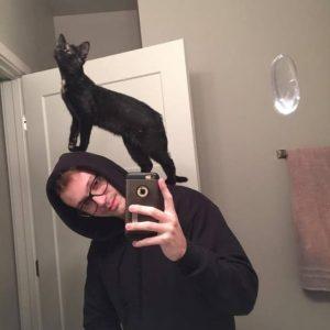 парень делает селфи с кошкой на плечах