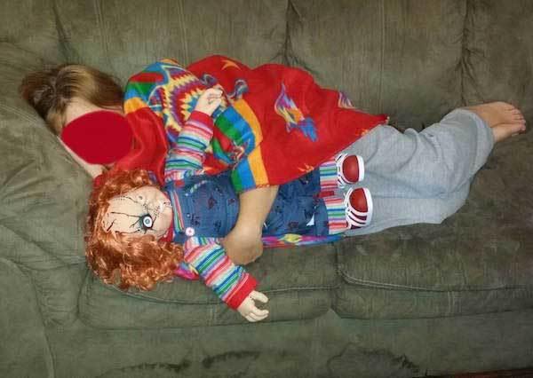 девочка спит с куклой на диване