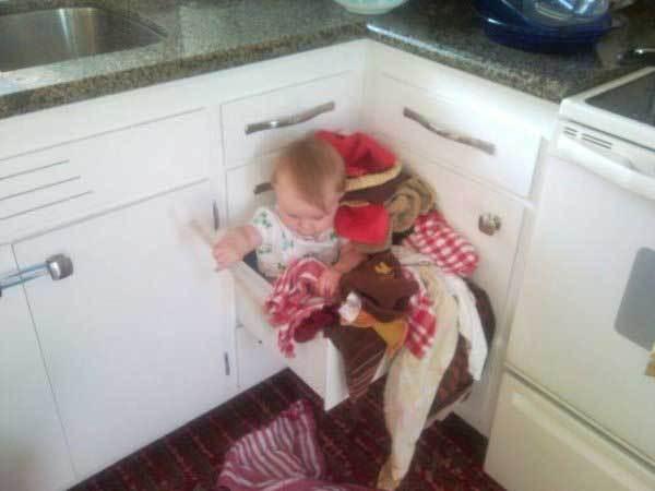 ребенок сидит в кухонном ящике