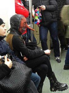 женщина в кожаной маске в вагоне метро