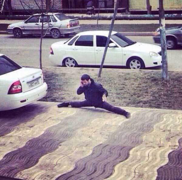 мужчина сидит на улице на шпагате