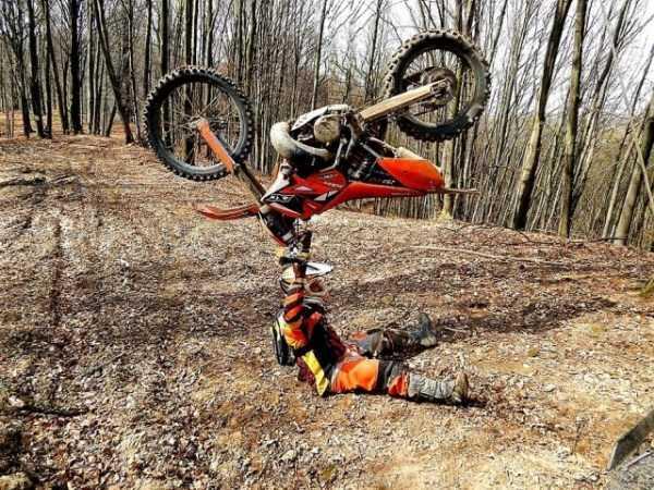 мотоциклист с мотоциклом над головой