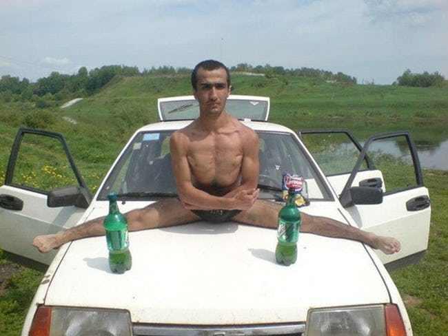 мужчина сидит на шпагате на капоте авто
